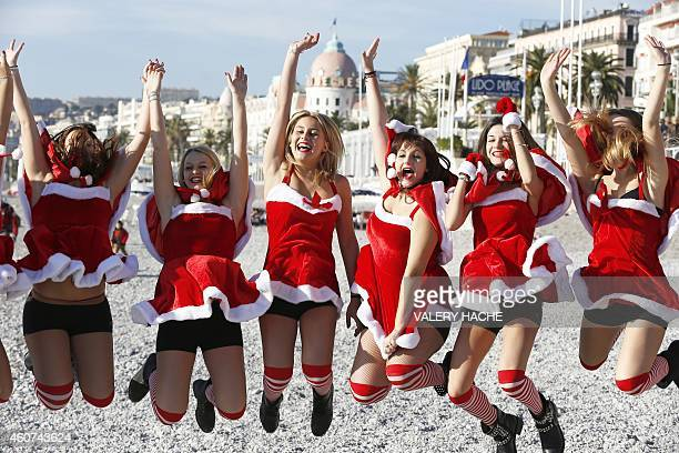 Young women dressed in Santa Claus outfit jump as they pose within the traditional Christmas bath on December 21 2014 on the beach in downtown Nice...