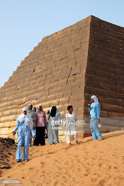 Young women dressed in tobes and hijabs visiting the Pyramids of Meroe in the Sahara desert Sudan North Africa