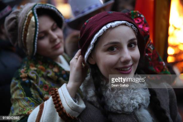 Young women dressed in traditional southern Lithuanian winter dress walk next to one of the many bonfires lit on Gedimino avenue in the city center...