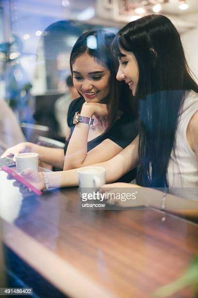 Young women drink coffee, using smart phone, coffee shop, Tokyo