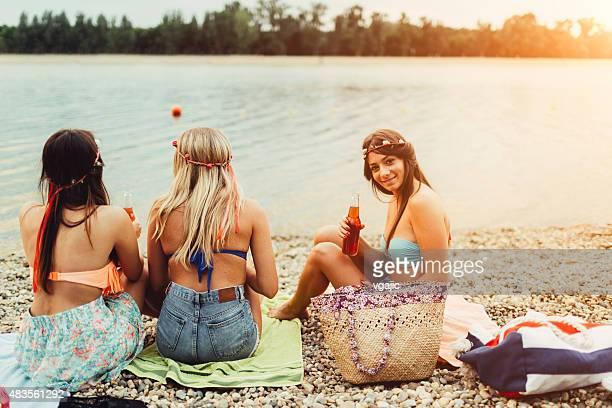 Junge Frauen trinken und reden auf den Strand.