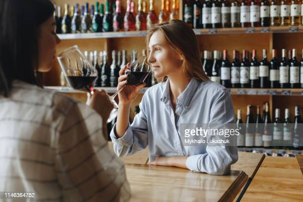 young women drinking red wine - wine tasting stock pictures, royalty-free photos & images