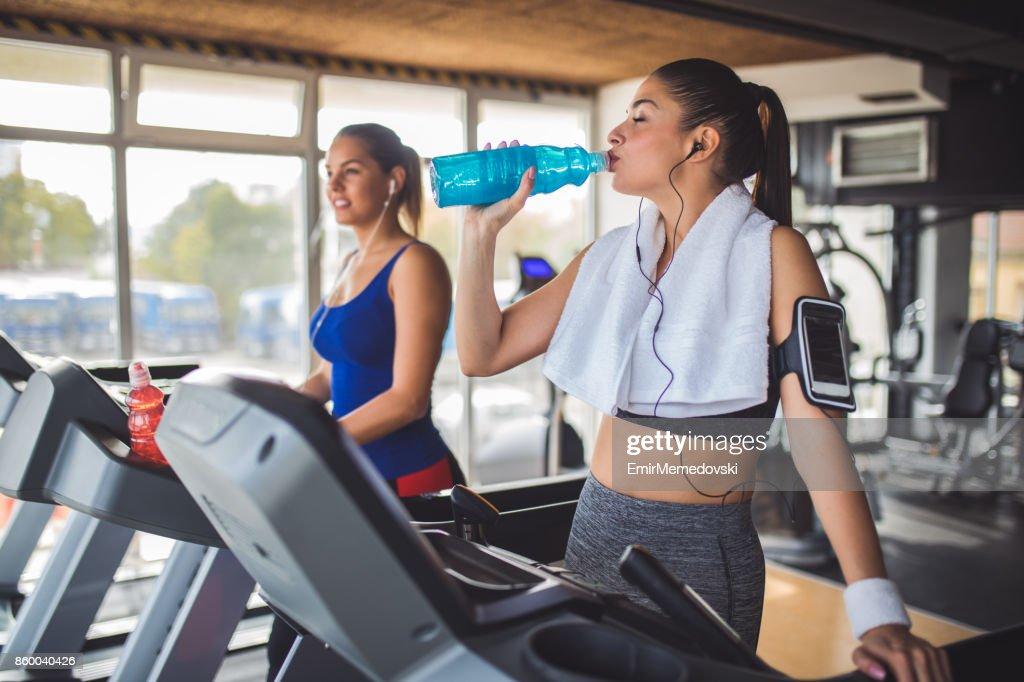 トレッドミル運動をしながら回復ドリンクを飲む若い女性 : ストックフォト