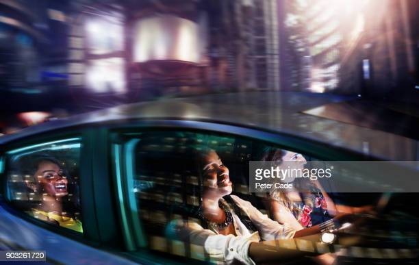 young women driving in car on night out - enjoyment stock pictures, royalty-free photos & images
