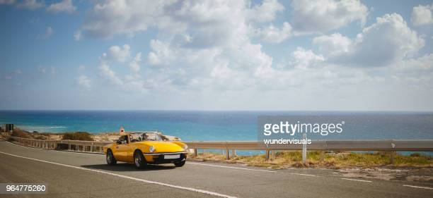 young women driving retro convertible car on seaside highway - coastline stock pictures, royalty-free photos & images