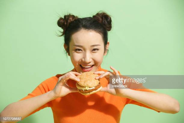 young women eat hamburgers - waist up stock pictures, royalty-free photos & images