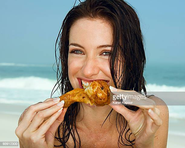 young women eating a chicken leg - fried chicken stock photos and pictures