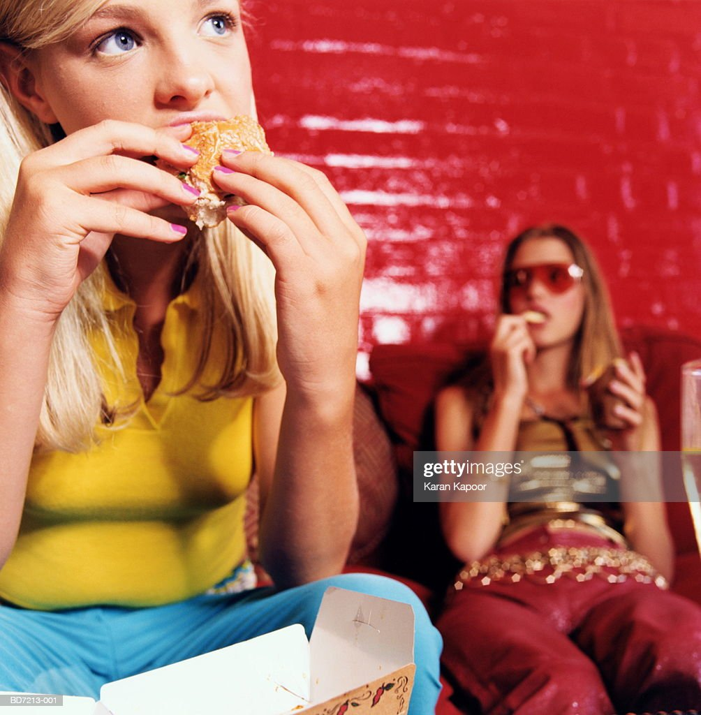 Young women eating, close-up : Stock Photo