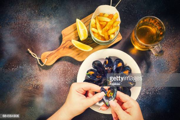 Young Women Eating Freshly Steamed Mussels Dish