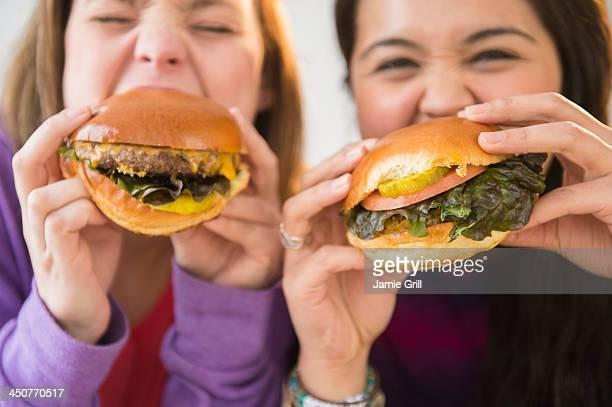 Young women eating hamburgers