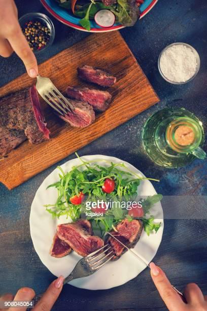 Young Women Eating Juicy Beef Steak