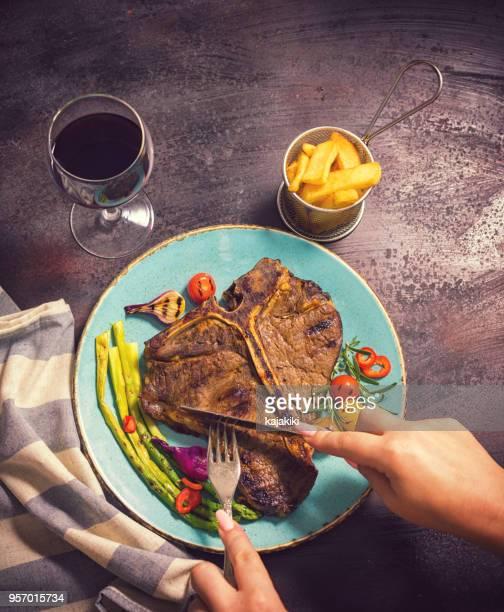 Young Women Eating Juicy T-Bone Steak