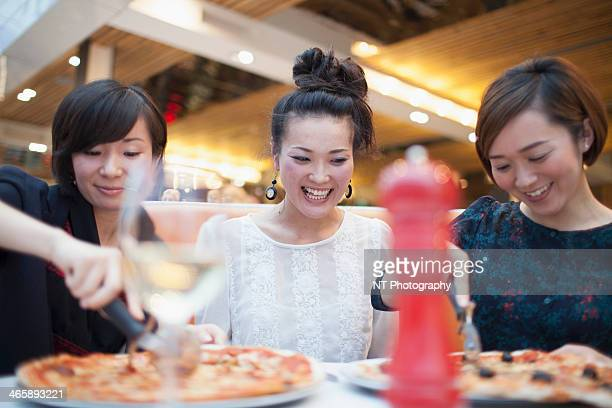 Young women eating pizza in restaurant