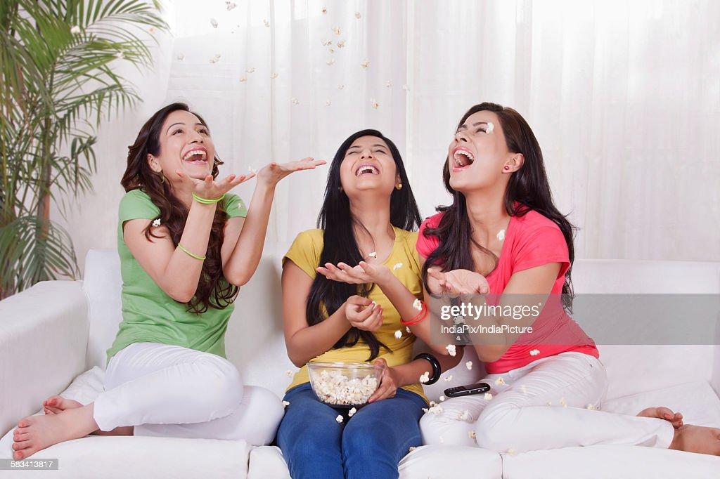Young women eating pop corn : Stock Photo