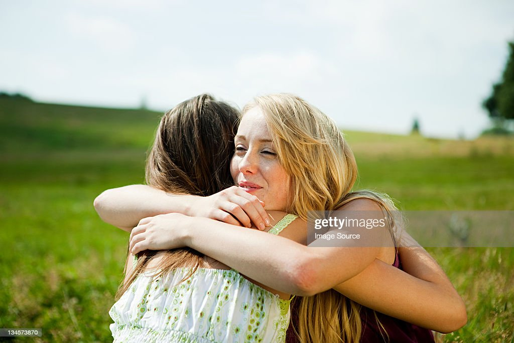 Young women embracing in a field : Stock Photo