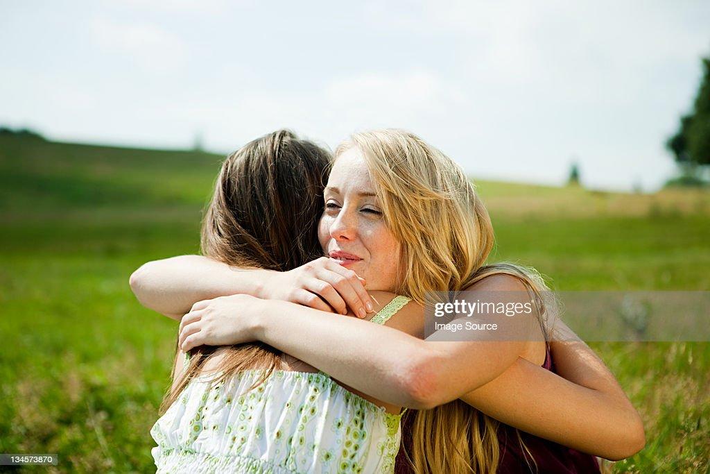 Young women embracing in a field : Bildbanksbilder