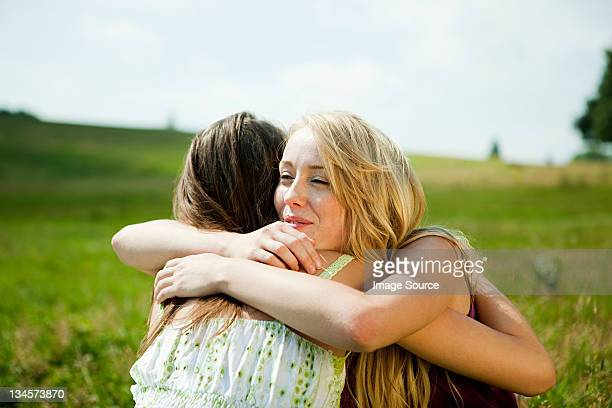 young women embracing in a field - reconciliation stock photos and pictures