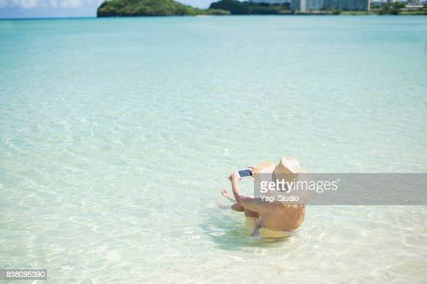 Young women enjoying and using a smart phone at beach in guam