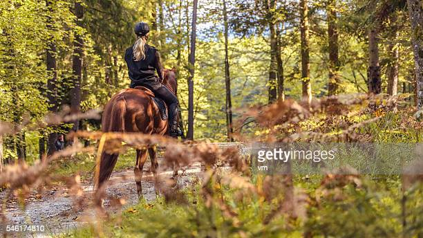 young women enjoying horseback riding in nature - andare a cavallo foto e immagini stock