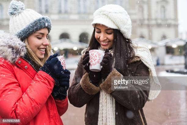 Junge Frauen genießen heiße Getränke am Wintermarkt