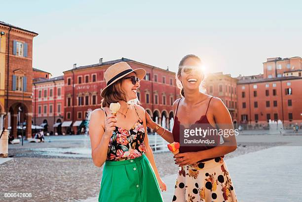 young women enjoying on the town square eating ice cream
