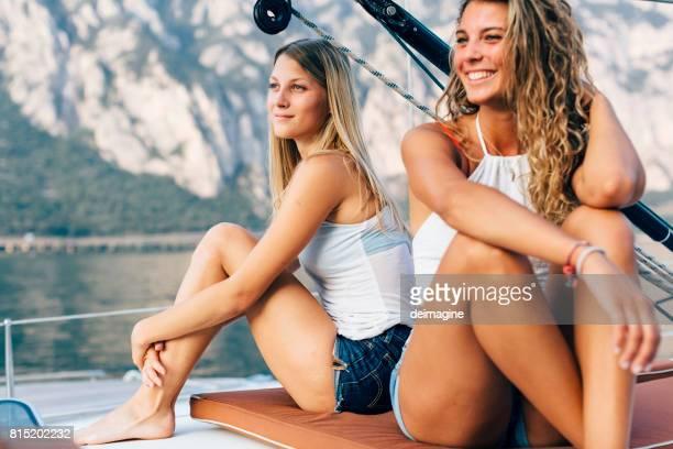 Young women enjoying the sun on sailboat at lake