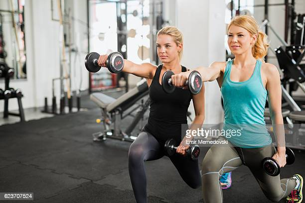 Young women exercising lunges with dumbbells at the gym