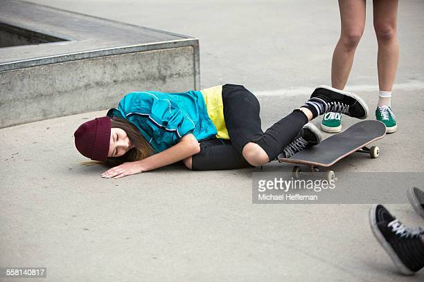 Young women falls off skateboard