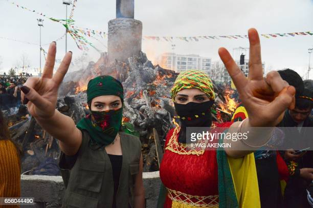 Young women flash the victory sign in front of a bonfire as Turkish Kurds gather during Newroz celebrations for the new year in Diyarbakir...