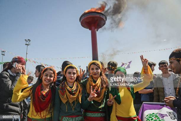 TOPSHOT Young women flash the victory sign in front of a bonfire as Turkish Kurds gather during Newroz celebrations for the new year in Diyarbakir...