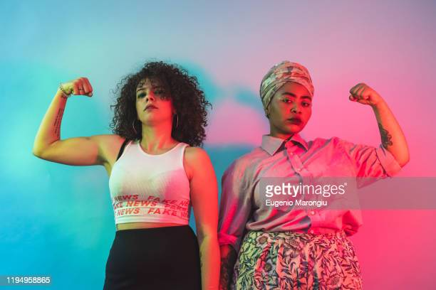 young women flexing arms against blue and pink background - hoofddeksel stockfoto's en -beelden