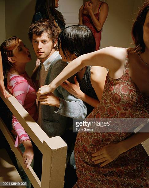 young women flirting with man at party, one leading him away - gigolo stock photos and pictures