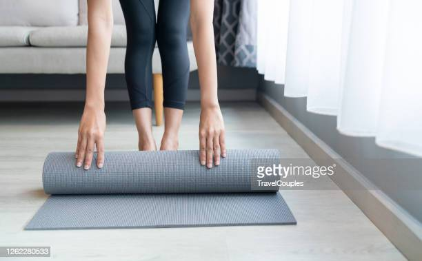 young women folding gray yoga or fitness mat after working out at home in living room. woman rolling her yoga mat after a workout. beautiful girl preparing material for practice class. female happiness and yoga concept. - エクササイズマット ストックフォトと画像