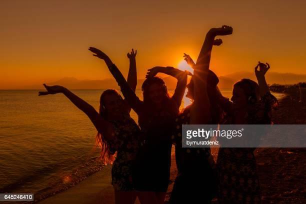 Amigos de las mujeres jóvenes bailando en la playa al atardecer
