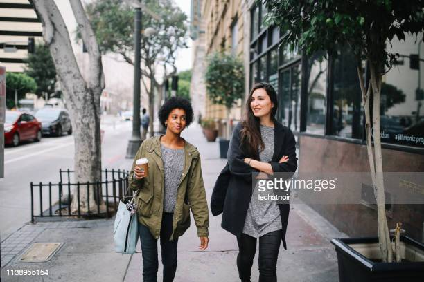 young women friends walking in los angeles downtown district - khaki green stock pictures, royalty-free photos & images
