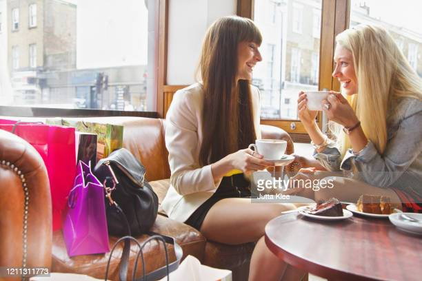 young women friends with shopping bags enjoying coffee and dessert in cafe - drink stock pictures, royalty-free photos & images