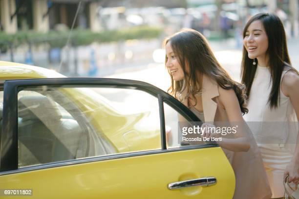 Junge Frauen, die ein Taxi nach dem Einkauf