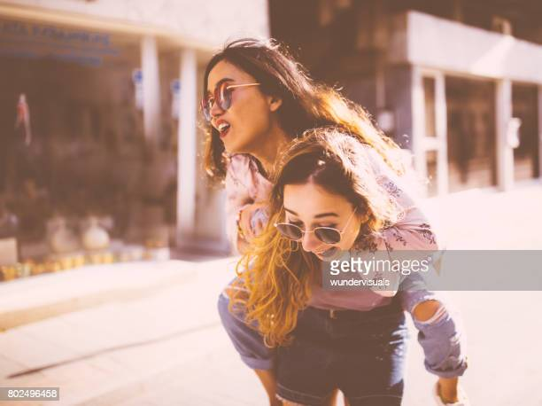 Young women giving a piggyback ride in old city streets