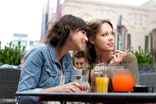 Junge Frauen gossiping Im sidewalk cafe