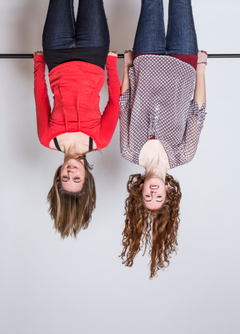 Young women hanging upside down, smiling - gettyimageskorea