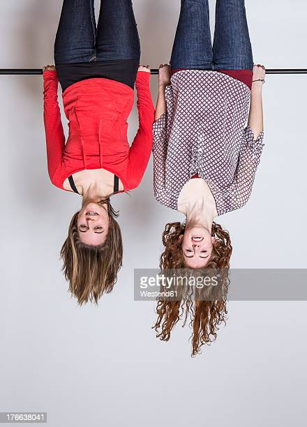 young women hanging upside down, smiling - op z'n kop stockfoto's en -beelden