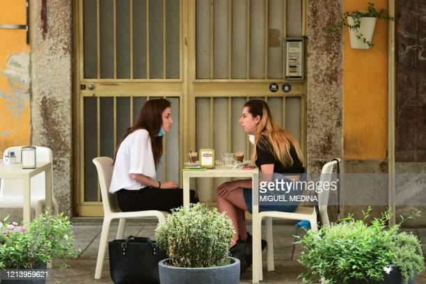 Young women have a drink at a cafe terrace in Codogno, southeast of Milan, one of the villages at the epicenter of the coronavirus epidemic in...