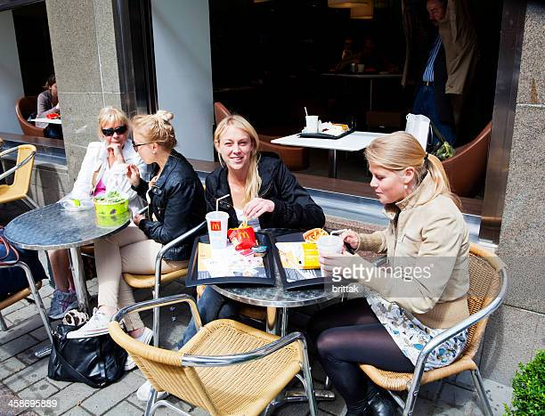 young women having a meal on the sidewalk outside mcdonalds. - mcdonald's stock pictures, royalty-free photos & images