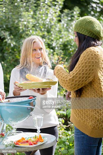 Young women having barbecue in garden