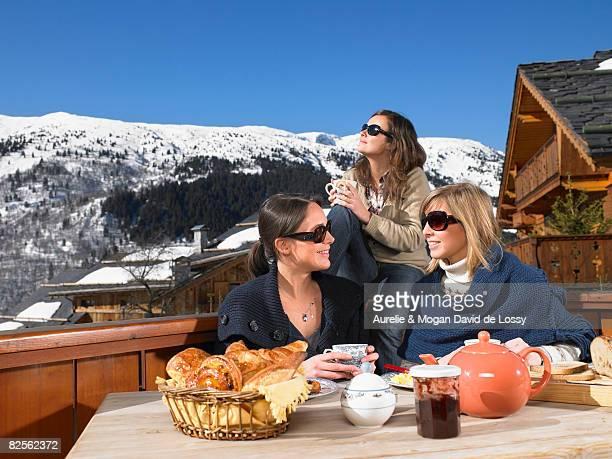young women having breakfast on terrace - meribel stock photos and pictures