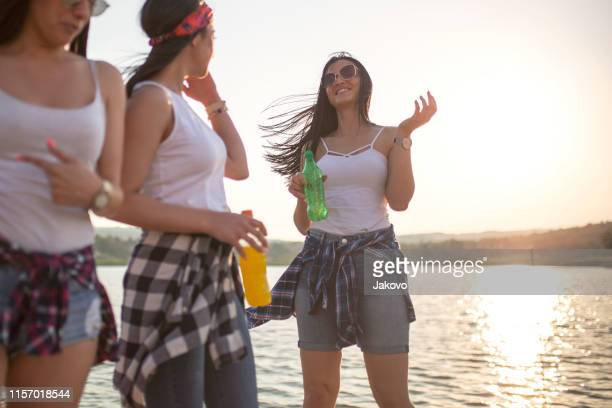 young women having fun by the lake - soda bottle stock pictures, royalty-free photos & images