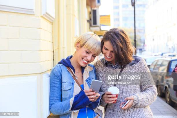 Young women having fun on street and using smart phone
