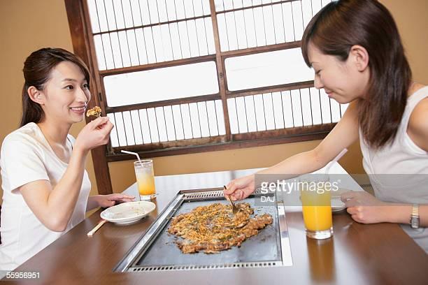 young women having japanese food, monjayaki - okonomiyaki stock pictures, royalty-free photos & images
