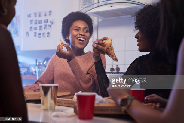 young women having party in the kitchen and eating pizza - menselijk lichaamsdeel stockfoto's en -beelden
