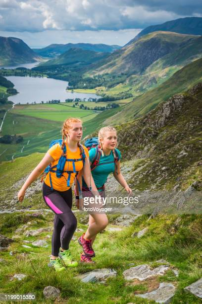 young women hiking up mountain trail above green valley lake - english lake district stock pictures, royalty-free photos & images